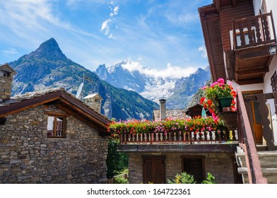Beautiful traditional house with flowers in Courmayeur, Italy, with fantastic view of Mont Blanc.