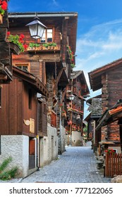 Beautiful traditional wooden houses in the streets of the alpine village Grimentz, Switzerland, in the canton Valais, municipality Anniviers, with geranium flowers on the balconies