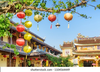Beautiful traditional yellow and red silk lanterns on green branches of tree at Phap Bao Temple area in Hoi An Ancient Town, Vietnam.