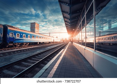 Beautiful train with blue wagons at the railway station at sunset. Industrial view with modern train, railroad, railway platform, buildings, sky with clouds in sunny evening. Railway tourism. Vintage