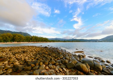 Beautiful tranquil cool natural rocky sea shore with fantastic views of the mountains with blue sky and clouds.
