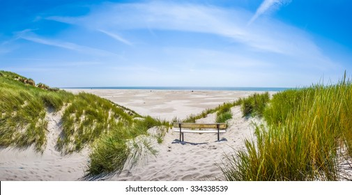 Beautiful tranquil dune landscape with idyllic bench overlooking the German North Sea and a long beach on the island of Amrum, Schleswig-Holstein, Germany