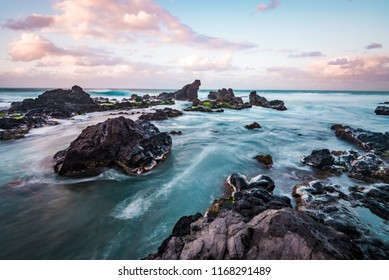 Beautiful Tranquil Long Exposure of  Relaxing Tropical Island Paradise From Sea Cliff Over Clear Blue Ocean Water and Waves Crashing on Rocks with Colorful Pastel Sunset Sky at Dusk on Maui Hawaii