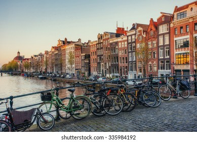 Beautiful tranquil scene of the city of Amsterdam. Bicycles along the street on the bridge over the canal.