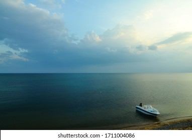 A beautiful and tranquil seascape. Sea background. Motor boat (boat) at the pier in the sea. Evening sky, quiet calm sea