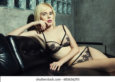 Beautiful transgender woman in lingerie on the couch