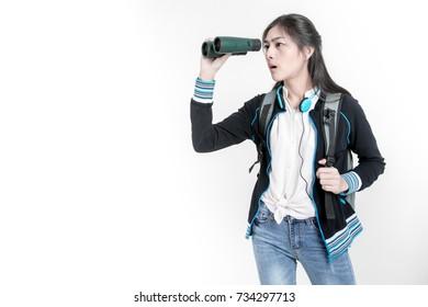 Beautiful Travel asian girl looking through binoculars, travel concept. Beautiful backpack travelller with earphone and binoculars. Studio shot on white background.