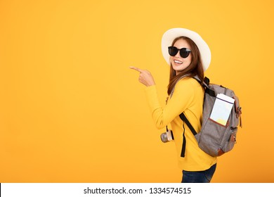 Beautiful traveler asian woman with camera and backpack Pointing away yellow background , summer trav