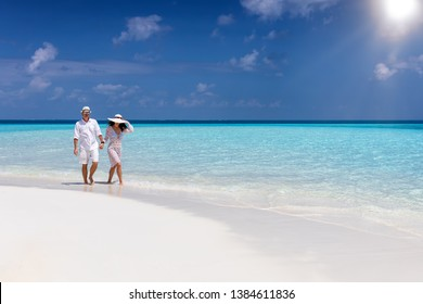 Beautiful traveler couple walks down a tropical beach with turquoise sea and sunshine in the Maldives islands