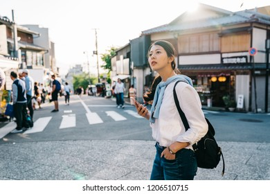 beautiful traveler crossing the road and looking at the online map to arrive at the hotel in Kyoto. tourist visit town using online japan travel guide app on smartphone.