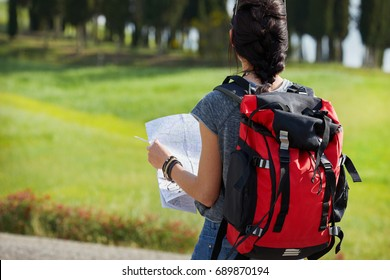 beautiful traveler woman carrying backpack walking on country road.