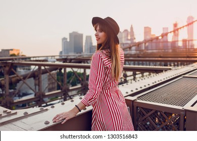 Beautiful traveling woman in red dress and stylish black hat enjoying amazing view from Brooklyn bridge in New York. Sunset colors. View from back.