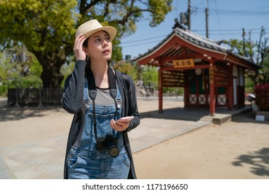 beautiful travle woman searching by phone and looking around to find something in the temple.