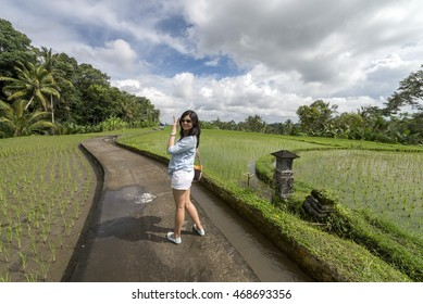 A beautiful trendy asian chinese lady with victory sign along pavement of paddy field at Ubud, Bali.