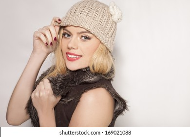 Beautiful trendy blond woman in winter fashion wearing a fur jacket and warm knitted cap standing sideways smiling at the camera