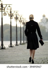 Beautiful trendy blonde lady walking over promenade