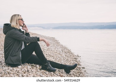 beautiful and trendy blonde woman talking on the phone at the beach in autumn. wearing a trendy bomber jacket with black jeans and black ankle boots. warm grade.