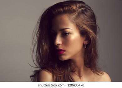 Beautiful trendy girl with fashionable makeup in a studio posing