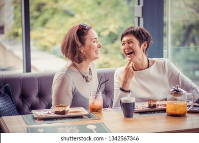 Beautiful trendy middle-aged women having coffee with desserts at table in cafe and laughing in leisure