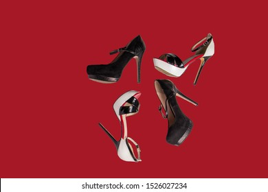 Beautiful trendy red black and white shoes with heels on a red-orange background are scattered