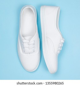 Beautiful trendy white shoes for women on a blue background. Flat lay, concept