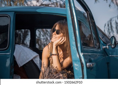 Beautiful trendy woman sitting in vintage car