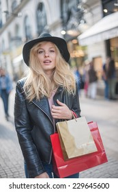 beautiful trendy young woman with hat and leather jacket doing shopping in the city, shopping bags in her arm