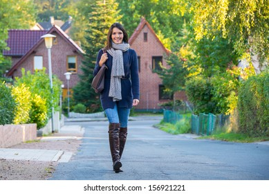 Beautiful trendy young woman in stylish clothing with a warm scarf and knee length boots walking down a rural road amongst houses in a leafy suburb