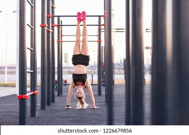 Beautiful trong young woman instructor in the gym doing handstand on the street of the playground sunny warm summer day. Concept of good physical shape and healthy lifestyle