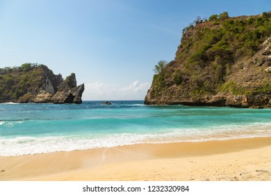 Beautiful tropical beach Atuh at Nusa Penida island. Turquoise ocean waves and sea rocks. Famous tourists point near Bali island, Indonesia