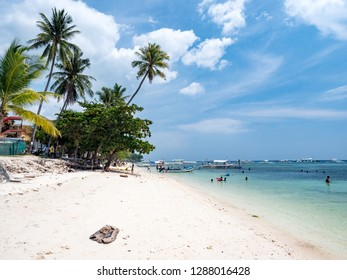 Beautiful tropical beach background from Alona Beach at Panglao Bohol island, the white sand beach with cloudy blue sky and palm trees. Travel Vacation, Philipines, november, 2018