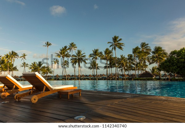 Beautiful tropical beach front hotel resort with swimming pool, sun-loungers and palm trees during a warm sunny day, paradise destination for vacations in Praia do forte, Bahia, Brazil.