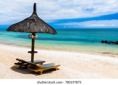 beautiful tropical beach with green coconut palms straw sunshades and wooden sunbeds in front of a turquoise sea with a blue sky, Mauritius, Africa