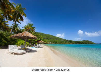 Beautiful tropical beach with palm trees, white sand, turquoise ocean water and blue sky at British Virgin Islands in Caribbean