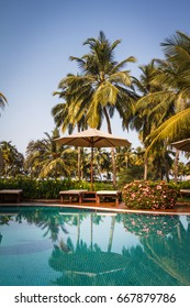 A beautiful tropical beach resort with wooden reclining sunbeds and parasol under shade of big palm trees next to swimming pool early in the morning without people.