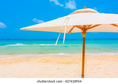Beautiful tropical beach and sea landscape with coconut palm tree and umbrella and chair - Boost up color Processing
