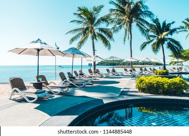 Beautiful tropical beach and sea with umbrella and chair around swimming pool in hotel resort for travel and vacation - Shutterstock ID 1144885448
