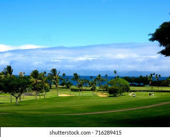 Beautiful Tropical Golf Course in Hawaii - Scene of the course including lush green fairways, palm trees, sand bunkers and the Pacific Ocean