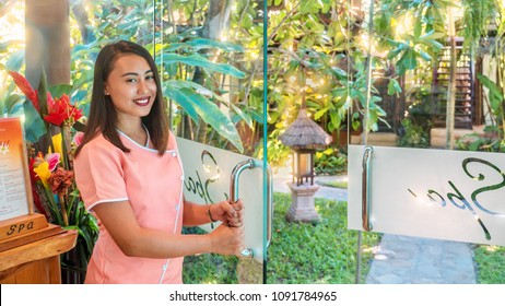 In a beautiful tropical island resort garden setting, an attractive southeast Asian spa employee, wearing a professional uniform, holds a glass door open with friendly smile. Philippines.