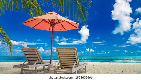 Beautiful tropical island scenery, two sun beds, loungers, umbrella under palm tree. White sand, sea view with horizon, idyllic blue sky, calmness and relaxation. Inspirational beach resort hotel