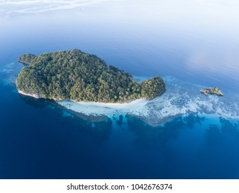 A beautiful tropical island is surrounded by peaceful seas in the equatorial seascape of Raja Ampat, Indonesia. This unique region is best known for its vast array of marine biodiversity.