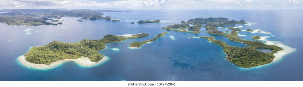 The beautiful tropical islands of Pef are surrounded by calm seas in the equatorial seascape of Raja Ampat, Indonesia. This unique region is best known for its vast array of marine biodiversity.