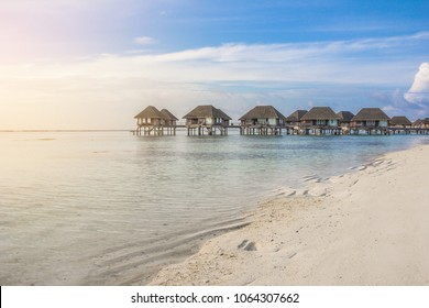 Beautiful tropical Maldives and island with beach and sea on sky for holiday vacation background concept. Water villas, Maldives island in sunset, holiday vacation destination.