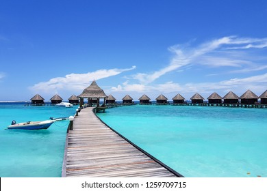 Beautiful Tropical Maldives Resort Hotel, The Turquoise Lagoon, Wooden Bridge And Blue Sky Day For Holiday Vacation Background.