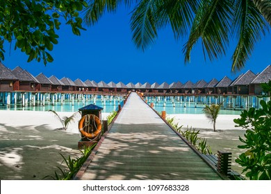 Beautiful tropical resort with wihte beach and turquoise water for relax on Olhuveli island, Maldives. White sand beach with a coral reef. Best beach for relaxation, sunbathing and snorkeling.
