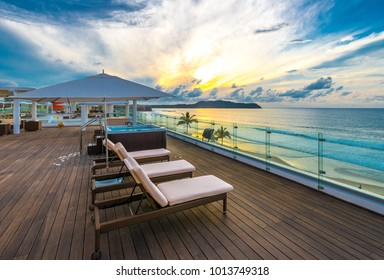 Beautiful tropical wooden deck at the ocean beach, resort at sunset, evening, sunrise time.