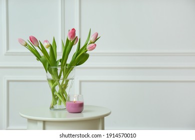 Beautiful tulips and burning candle on white table indoors, space for text. Interior design