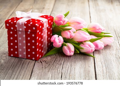 beautiful tulips with red polka-dot gift box. happy mothers day, romantic still life, fresh flowers. on wooden background