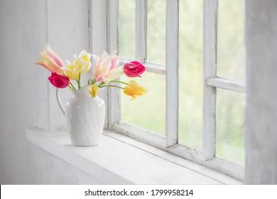 beautiful tulips in vase on white windowsill - Shutterstock ID 1799958214