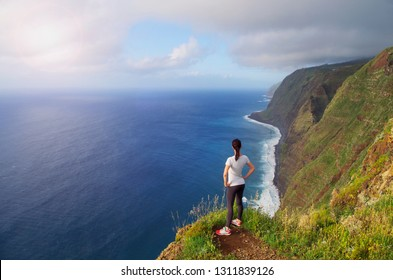 Beautiful tuorist woman stay on most western Extreme point of the island Madeira. View from Lighhouse Ponta do Pargo in Madeira the highest in Portugal